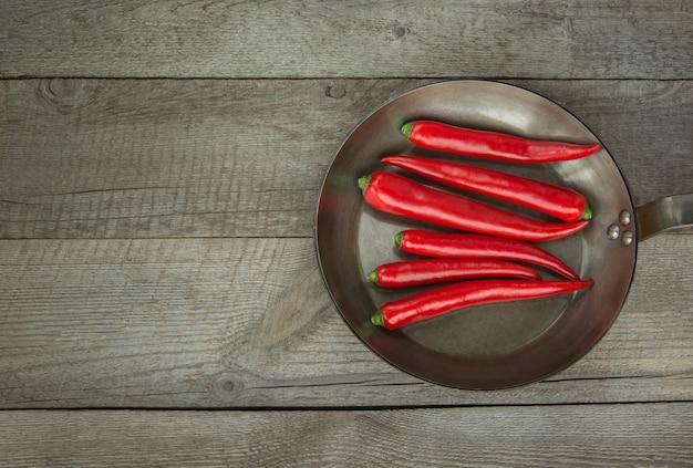 Red hot chili peppers e panela na placa de madeira vintage. vista superior com espaço de cópia.