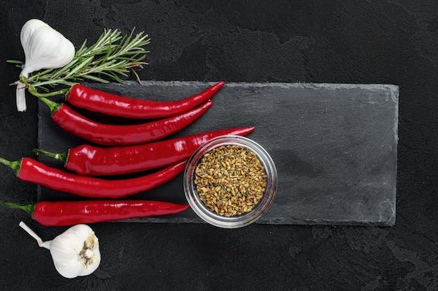 Red hot chilli peppers e outras especiarias em fundo escuro