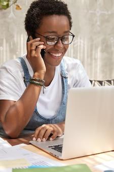 Redator alegre e ocupado trabalha como freelance em um laptop