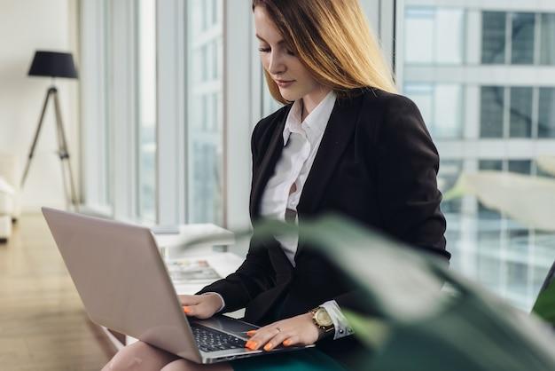 Redator feminino jovem, escrevendo um texto publicitário, digitando no teclado do laptop, sentado no escritório.