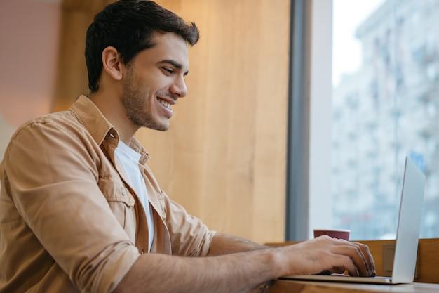 Redator indiano sorridente usando laptop trabalhando em projeto freelance de casa