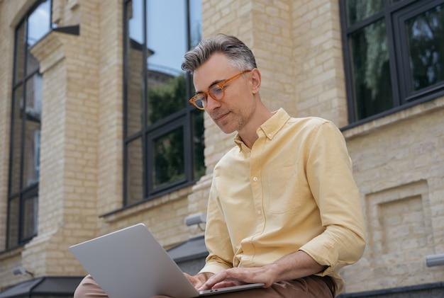 Redator maduro bonito usando laptop, trabalhando em projeto freelance, digitando