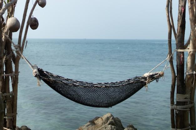 Rede amarrada rochas com vista para o mar.