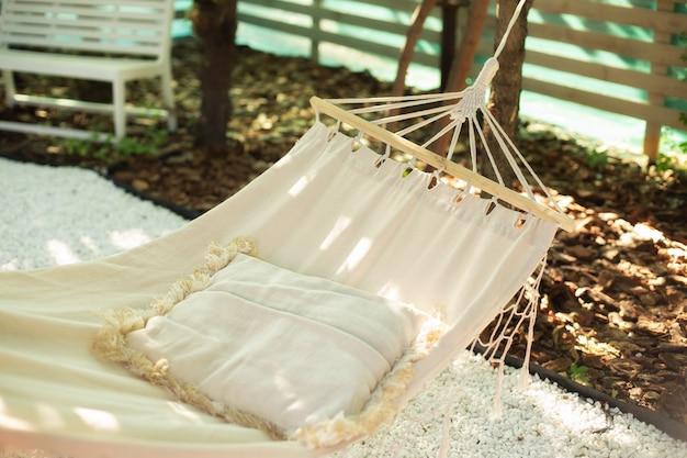 Rede branca no estilo boho e travesseiro para relaxar pendurado na árvore no jardim do quintal