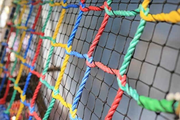 Rede colorida da corda amarrada para a escalada. dentro de casa playground.