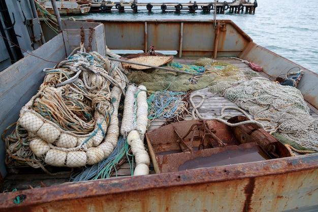 Rede de arrasto, pranchas pelágicas e rede de pesca no convés de pesca de um pequeno cercador