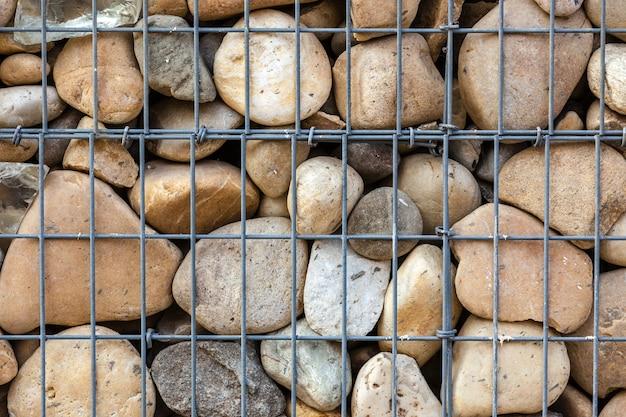 Rede de cesta metálica preenchida por pedras naturais como cerca