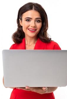 Rede de comunicação. morena de vestido vermelho em um isolado detém um laptop nas mãos