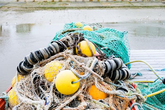 Rede de pesca azul em um pontão com suas cordas e carros alegóricos cobertos com geada da manhã