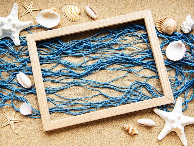 Rede de pesca e moldura de madeira na areia da praia
