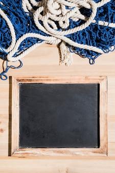 Rede de pesca sobre o quadro negro em branco sobre a superfície de madeira
