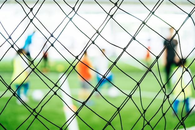 Rede de treinamento de futebol blur no campo de treinamento com crianças