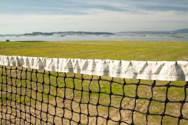 Rede de vôlei de praia envelhecida com mar