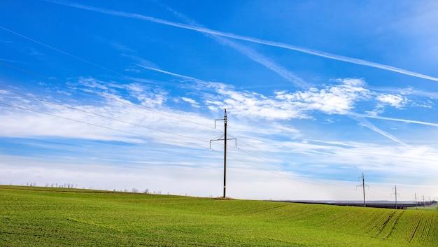 Rede elétrica e campo verde com paisagem de céu contrastante