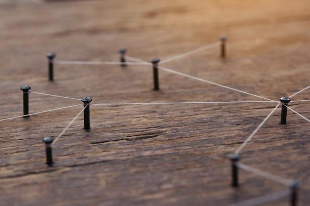 Rede feita por um fio entre pregos na placa de madeira