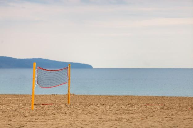 Rede vazia de voleibol em uma praia arenosa na costa do mar no verão.
