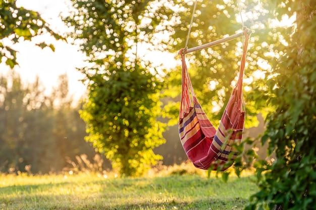 Rede vazia no jardim perto da árvore nas luzes do pôr do sol, conceito de descanso ao ar livre