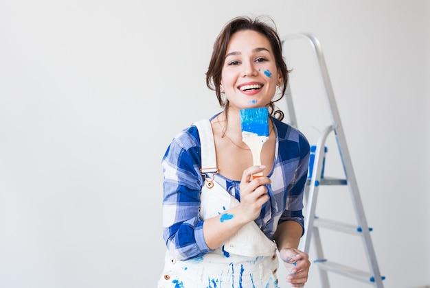 Redecoração, renovação e conceito de pessoas - jovem pintando a parede e se parece muito