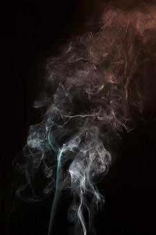Redemoinho de fumaça branca e turquesa contra fundo escuro preto