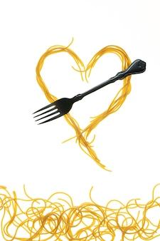 Redemoinhos de espaguete cozido com garfo. forma de coração de espaguete.