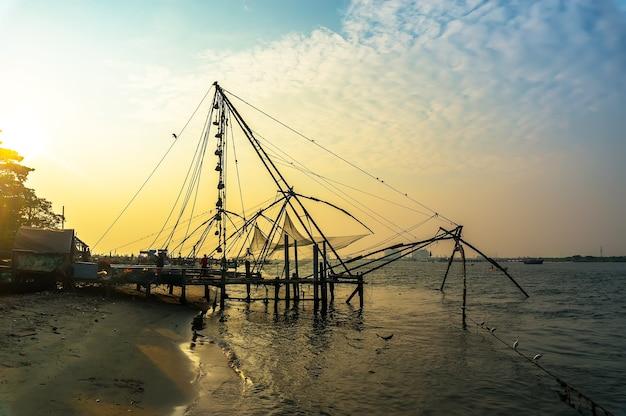 Redes de pesca chinesas na costa do mar da arábia. fort cochin, kerala, índia. marco histórico. noite quente. contornos cênicos no crepúsculo do pôr do sol. disco solar brilhante. cores delicadas e suculentas.