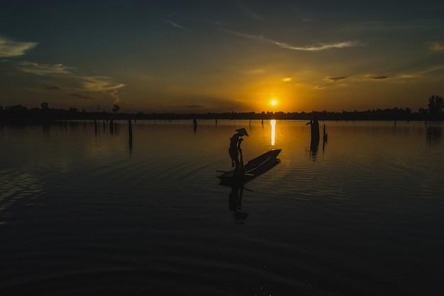 Redes de pesca do pescador da silhueta no barco.