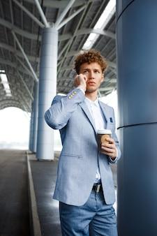 Redhaired empresário falando no telefone na rua segurando a xícara de café