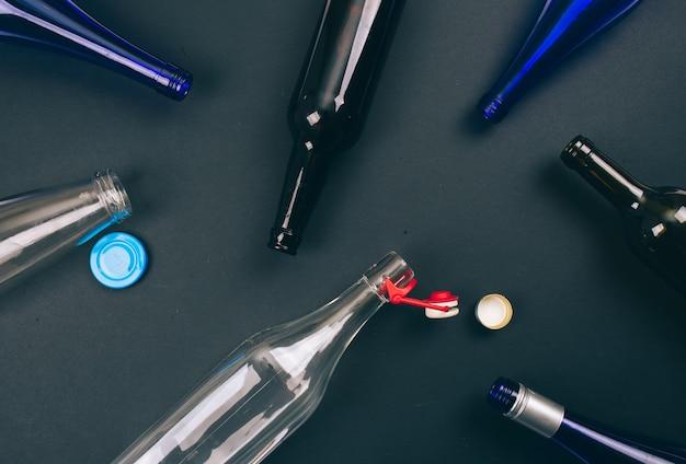 Reduzir, reutilizar, reciclar. as garrafas e tampas de vidro colorido vazio são preparadas para a reciclagem no escuro.