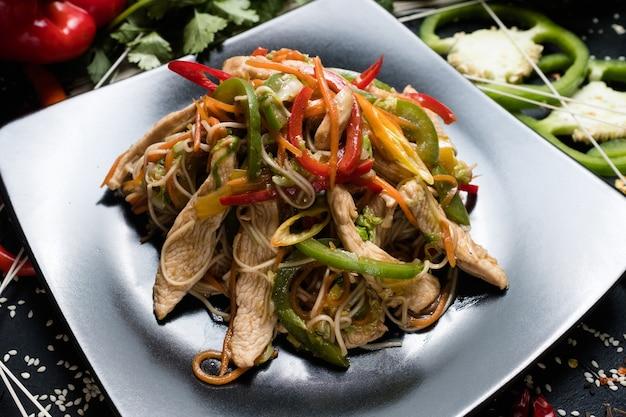 Refeição asiática tradicional caseira. salada de macarrão com frango e vegetais
