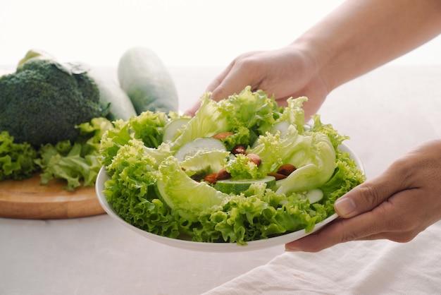 Refeição de café da manhã vegan verde em uma tigela com alface, pepino, limão e amêndoa. menina segurando o prato com as mãos visíveis, vista superior. alimentação limpa, dieta e conceito de comida vegana