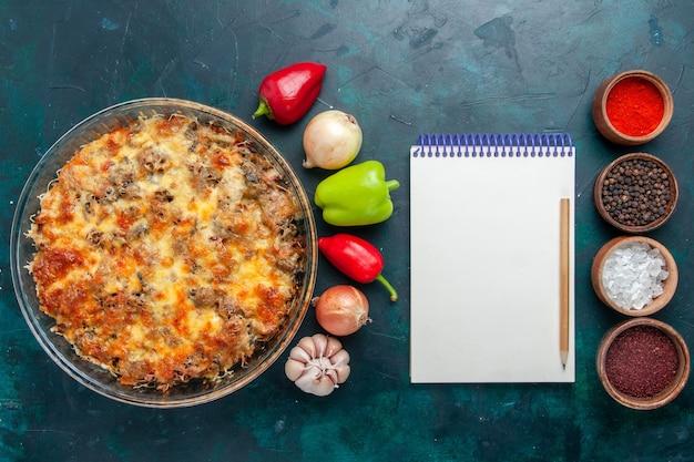 Refeição de carne de queijo com legumes frescos e temperos na mesa azul-escura vista de cima