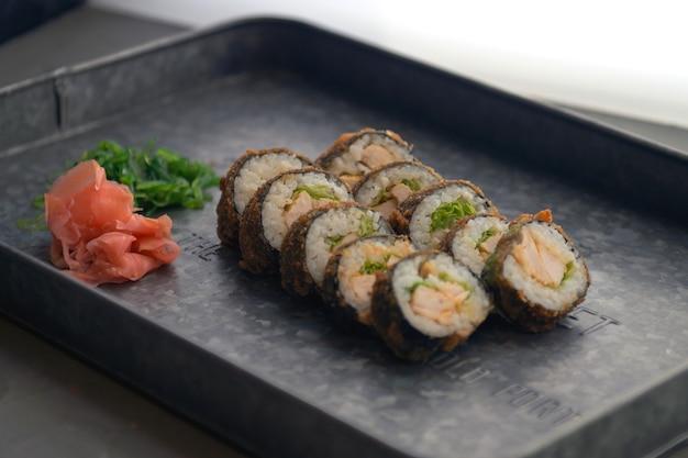 Refeição de sushi com gengibre e wasabi em prato de metal sushi set diferentes tipos de maki sushi e nigiri