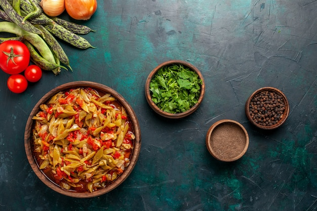 Refeição de vegetais fatiada com diferentes ingredientes dentro do prato na mesa azul escura