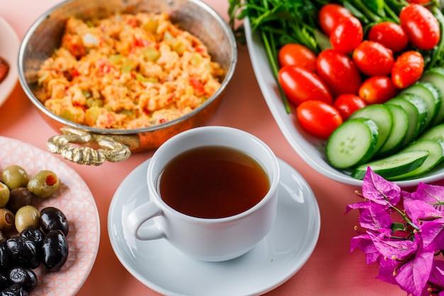 Refeição deliciosa em uma panela com uma xícara de chá, azeitona, salada, vista de alto ângulo de flores em uma superfície rosa