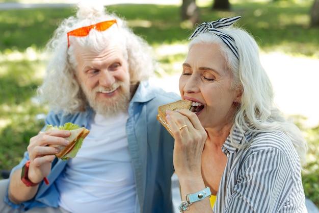 Refeição deliciosa. mulher positiva e encantada mordendo um sanduíche enquanto saboreia a refeição junto com o marido