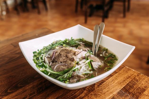 Refeição deliciosa. sopa com legumes e carne em um prato de cerâmico branco. pho bo.