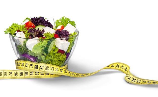 Refeição dietética. salada de legumes em uma tigela com fita métrica