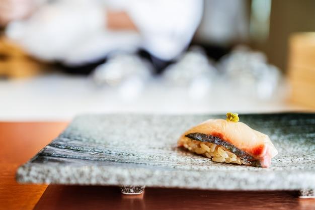 Refeição japonesa omakase shima aji sushi com wasabi fresco servido à mão em um prato preto de pedra. refeição japonesa tradicional e luxuosa