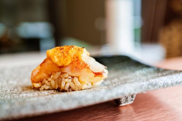Refeição omakase japonesa sushi de camarão grelhado com molho mentaiko torched servido à mão em um prato de pedra