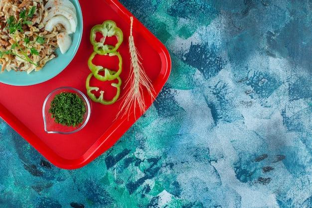 Refeição para um com vegetais fatiados na bandeja, na mesa azul.