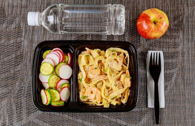 Refeição pronta no recipiente de alimento com água e maçã.