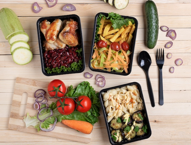 Refeição pronta para comer em recipientes de comida, asas de frango frito e legumes