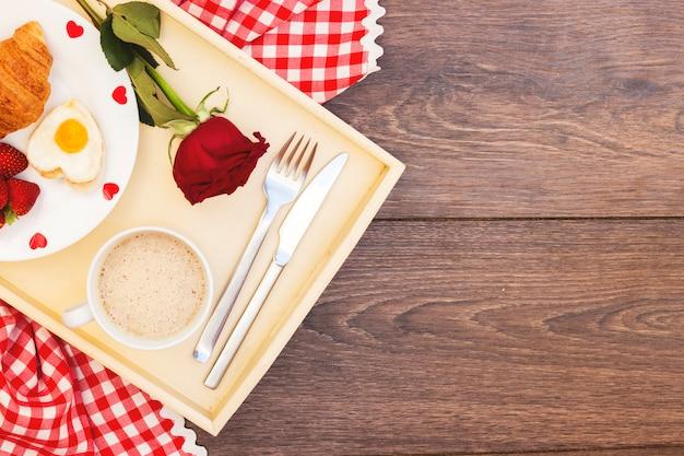 Refeição romântica na bandeja com rosa vermelha