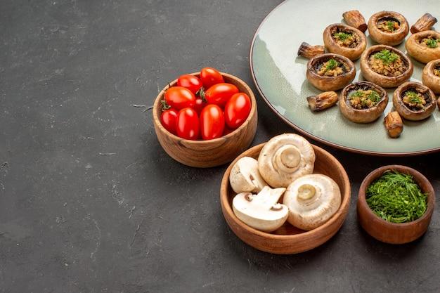Refeição saborosa de cogumelos com verduras frescas e tomates no fundo escuro prato de jantar cozinhando cogumelos