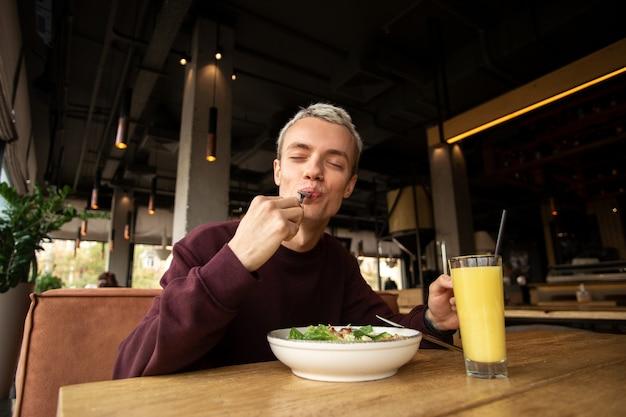 Refeição saborosa em um restaurante. homem louro muito emotivo de camisola vermelha a comer salada césar e sumo de laranja fresco