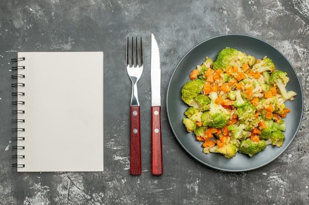 Refeição saudável com brocoli e cenoura em um prato preto com garfo e faca ao lado do caderno