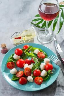 Refeição saudável com tomate cereja, bolas de mussarela, especiarias