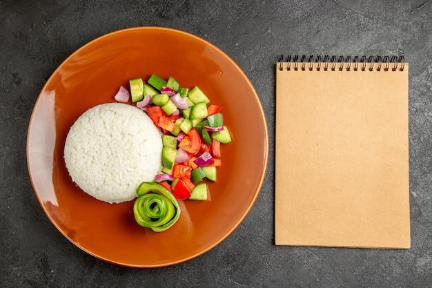 Refeição saudável fácil e caderno em fundo escuro