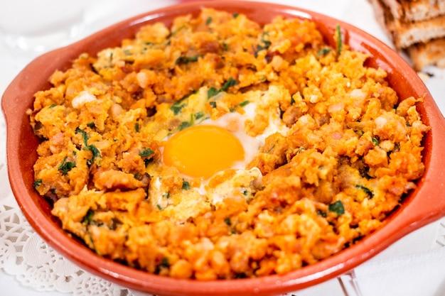 Refeição tradicional portuguesa de alheira mista com ovo e salsa.