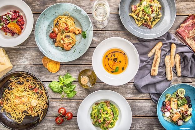 Refeições italianas do topo da vista em pratos e panela d. sopa de risoto de macarrão e salada de legumes de peixe.